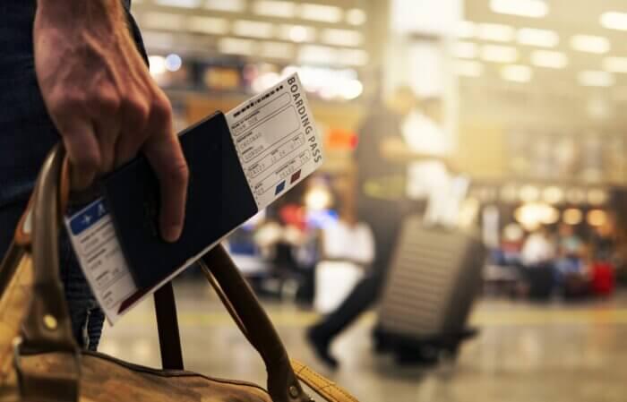 pessoa no aeroporto com a mala e passaporte nas mãos indo para um dos países que não precisam de visto para morar